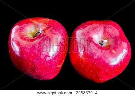 Two big red ripe appetizing apples on black background