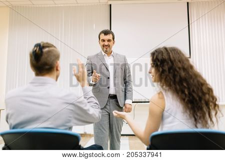Mature businessman giving a speech at the meetup on a blurred room background. Young students listening to a teacher.