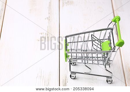 Empty Shopping Cart On A White Wooden Background