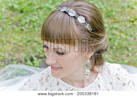 Portrait of beautiful smiling bride with diadem in the summer park