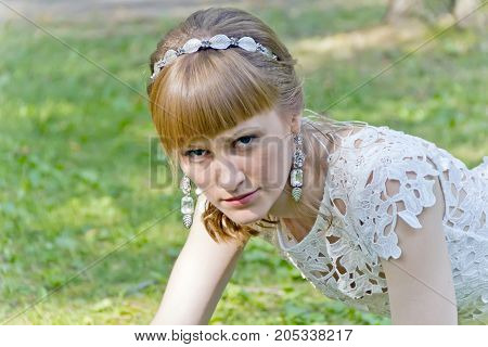 Beautiful portrait of serious bride with diadem in summer background