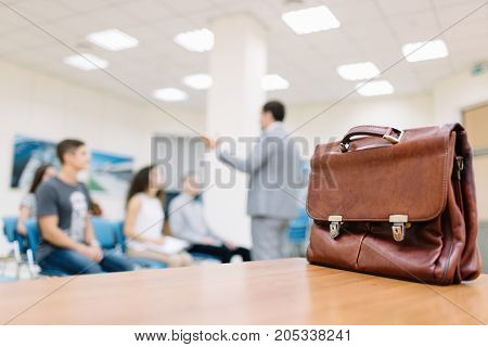 Close-up of a classic leather briefcase on a table on a blurred classroom background. Briefcase for documents. Copy space.