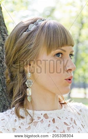 Beautiful portrait of talking bride with diadem in summer background