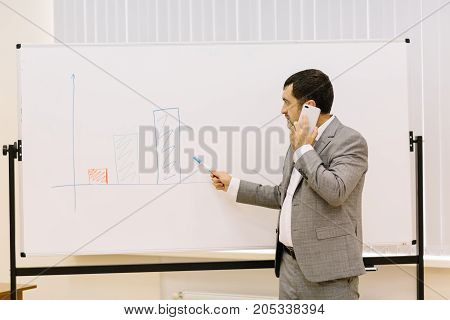 Progressive business man showing a presentation on a new multimedia projector on the conference room background. Copy space.