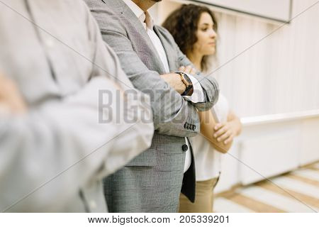 Close-up successful businessman standing with two confident office workers on a room background. Young people in business corporations.