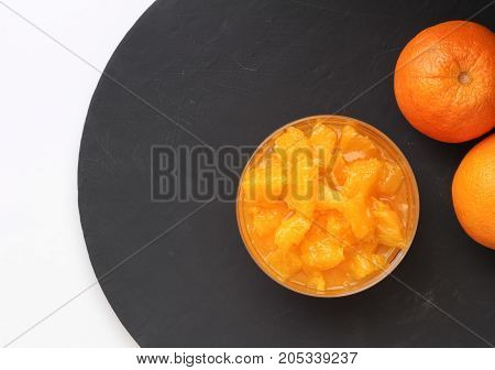 Orange slices in pudding bowl on black round slate with two whole oranges on the side. Top view food background with space for text