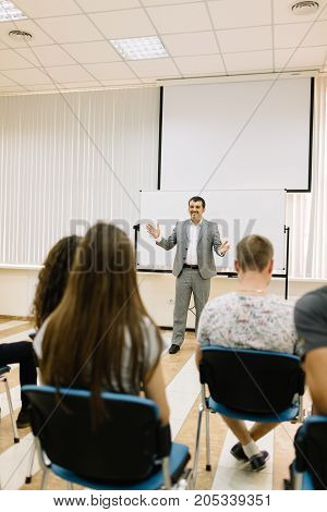 A happy, smiling businessman speaking on a conference with young students on a classroom background. Start-up convention for future companies.