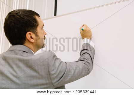 Close-up of a businessman in a suit working on a multimedia projector on a room background. Financial business work concept.