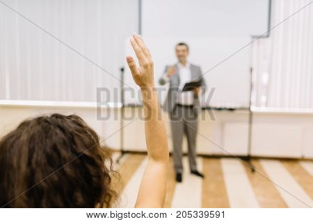 Student girl raising up hand for an answer on a classroom background. Teacher pointing at the student on a presentation. Copy space.