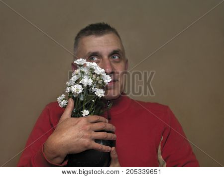 Funny looking man holding a vase with beautiful chrysanthemum studio filtered portrait