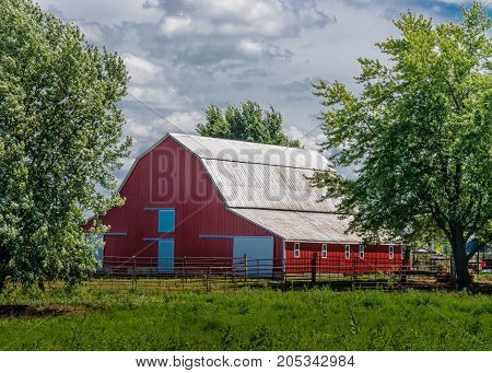 Red barn in a farmstead setting, clouds in blue sky with green trees framing the photo, beautiful and relaxing just waiting for the cattle to show.
