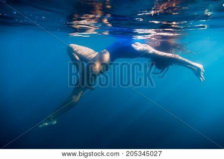 Woman floating in sea, underwater in blue ocean