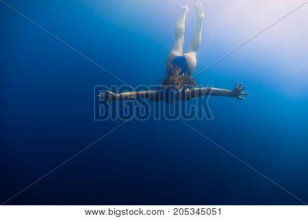 Sporty woman with bikini in underwater. Free diving in blue ocean, Bali