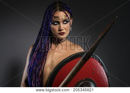 Sexy resolute horsewoman with African braids hairstyle, temporary gold tattoo on her face and bright makeup topless holding a spear and a red shield in her hands cropped portrait poster