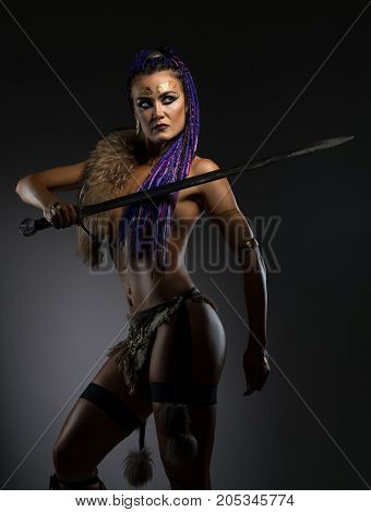 Sexy resolute horsewoman with African braids hairstyle, temporary gold tattoo on her face and bright makeup in original leather underwear and fur on her shoulder holding a sword in her hand on dark background cropped shot