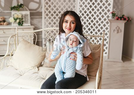 Newborn mixed race baby boy and his young mother. Asian and British new born baby