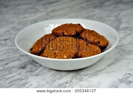 Homemade cookies with oatmeal with dried fruit and honey on a marble table