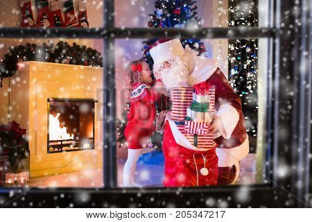 Children and Santa Claus at fireplace on Christmas eve. Family celebrating Xmas. Decorated living room with tree gifts fire place candles. Winter evening at home for parents and kids.
