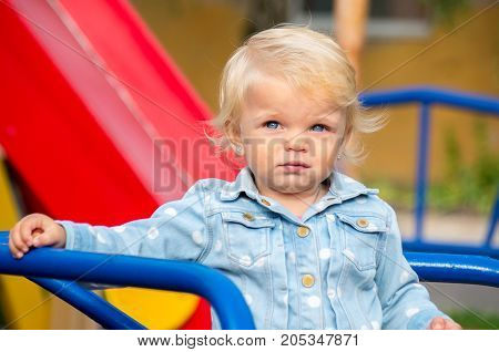 Portrait Of A Blonde Girl With Blue Eyes On A Playground