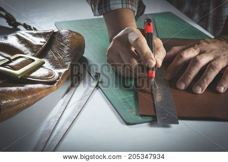 Close-up of male hand cutting with a knife to leather for bag. Home made product concept.