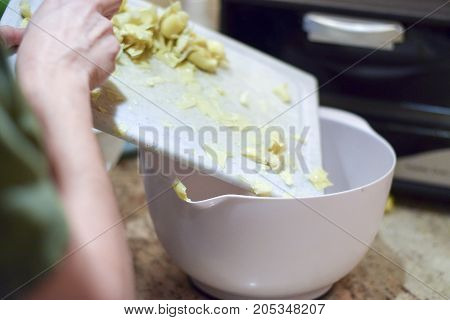 Hand Scraping Food Into Bowl