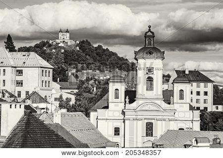 Calvary and Church of the assumption in Banska Stiavnica Slovak republic. Sunset urban scene. Travel destination. Black and white photo.