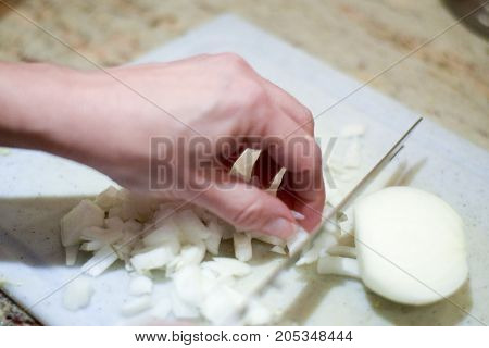 Hand Chopping Onion On Cutting Board