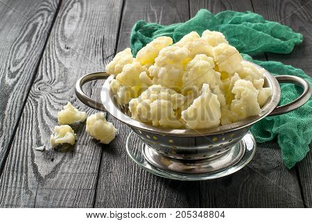 Blanched cauliflower in colander on gray wooden background. White cauliflower inflorescences in metal colander green gauze napkin on table. Preparing for diet dinner poster