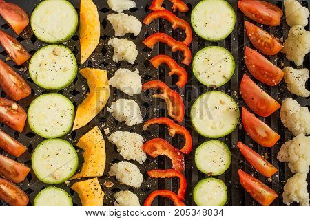 Variety of fresh vegetables prepared for cooking on grill pan. Vegetables are cut into pieces sprinkled with salt and spices laid in rows. Healthy and vegetarian food concept. Top view flat lay
