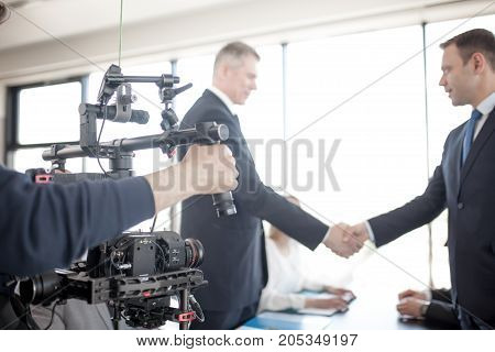 Videographer using steadycam making video of business people shaking hands