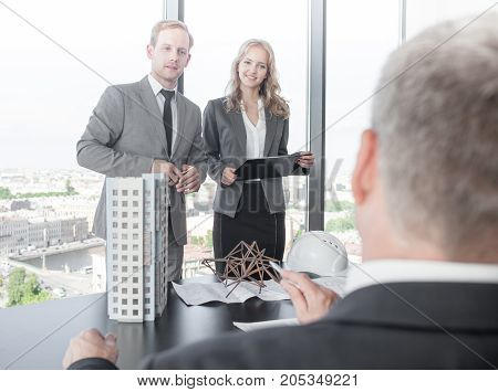 Business presentation of architects for investors discussing new construction shapes model of modern multi storey residential building house blueprints and hardhat on table