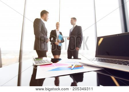Mixed group of people in business meeting working with documents and computers