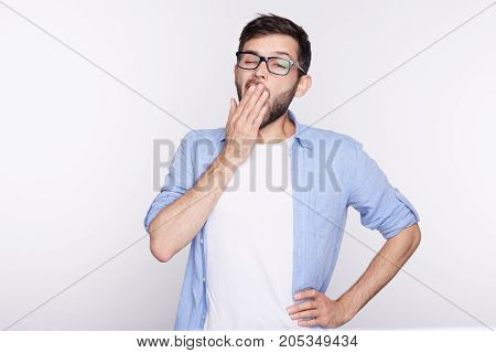 Tired or bored Caucasian hipster young man covering mouth while yawning feeling exhausted after hard day at work. Handsome male student having sleepy boring look before the meeting he doesn't like.