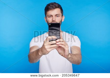 Cheerful young Caucasian hipster holding generic mobile phone and smiling broadly while taking selfie. Always in touch. Selective focus on hand with gadget. People modern lifestyle and technology.