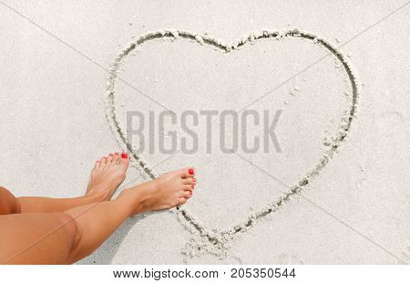 Girl Is Drawing Heart On The Sand.