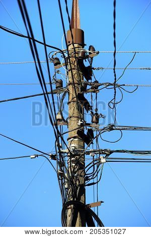 Entangled wires on the pole. Electrician services.