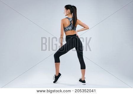 Beautiful and sexy sport woman posing back to the camera in studio over gray background