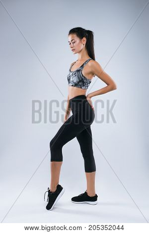 Beautiful and sexy sport woman posing  in studio over gray background