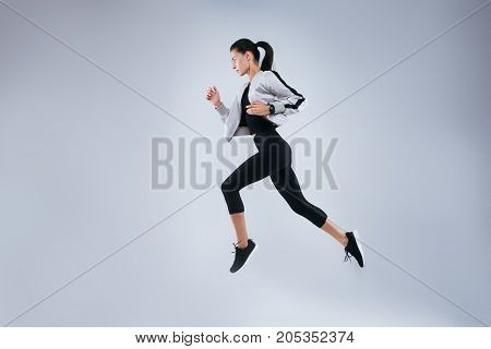 Vertical image of sports woman running over gray background. Fitness young woman doing morning running.