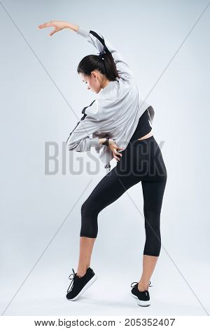 Slim and sport young woman posing and doing sport exercises standing with her back to the camera and stretching arms and back in studio isolated over gray background