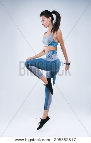 Full length portrait of a young healthy woman in sportswear posing and jumping isolated over gray background