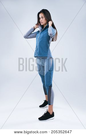 Beautiful strong woman dresses hood sportswear and listening to music in earphones while standing isolated over gray background.