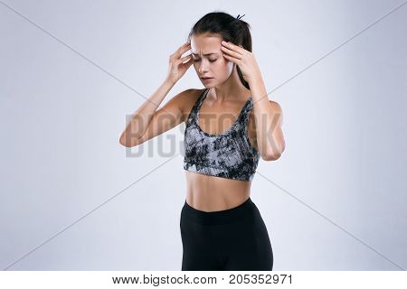 Young fitness woman in pain suffering from a strong migraine while standing isolated over gray background