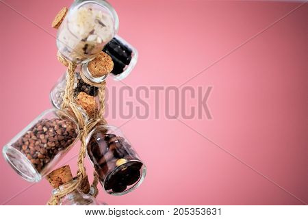 Quinoa, bulgur and couscous cereals. Vegetarian and dieting food concept. Cereals in glass jars are amused by a linen lace on is dusty a pink background