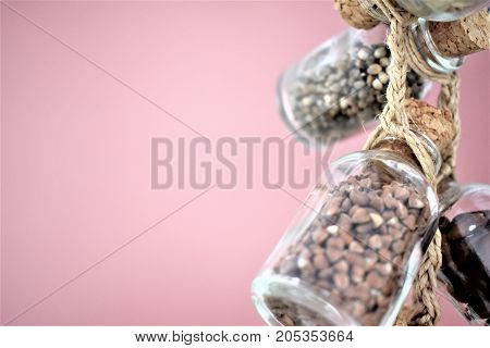Collection of grain products, lentils, soybeans and red beans in storage jars over on free background. Quinoa, bulgur and couscous cereals. Vegetarian and dieting food concept. Cereals in glass jars are amused by a linen lace on is dusty a pink background