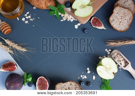 Preparation of breakfast. Oatmeal figs apples croissant honey and bread on a gray background. View from above