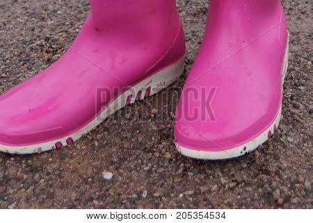Pink rubber child rain boots on a dirt road