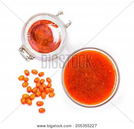 Fortified jam from fresh berries of sea buckthorn mashed with sugar in a glass jar and a vase isolated on white background