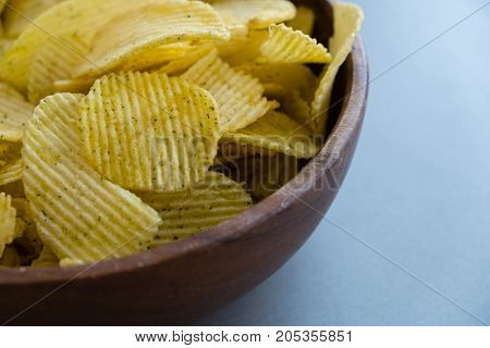 Potato chips in bowl on a grey background, top view. Salty crisps scattered on a table