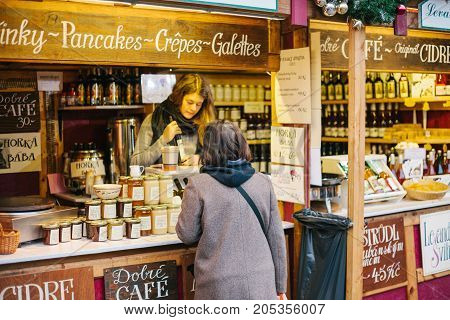 Prague, December 15, 2016: The seller offers the buyer a wide selection of honey and various wines. Christmas Market. Christmas shopping. Celebrating Christmas.